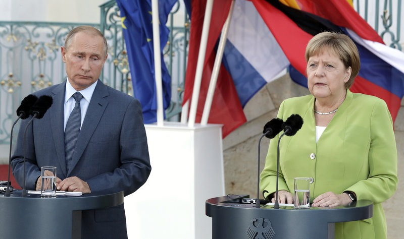 German Chancellor Angela Merkel, right, and the President of Russia, Vladimir Putin, left, address the media during a joint statement prior to a meeting at the government guest house Meseberg in Gransee near Berlin, Germany, Saturday, Aug. 18, 2018. (AP Photo/Michael Sohn)
